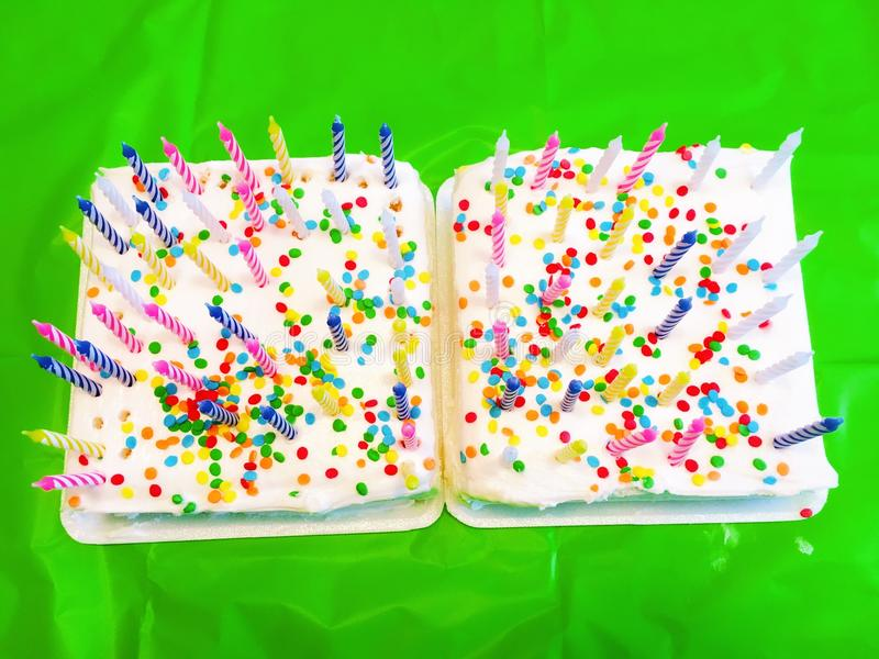 Birthday cakes with candles. Two birthday cakes on the table with candles light up royalty free stock images