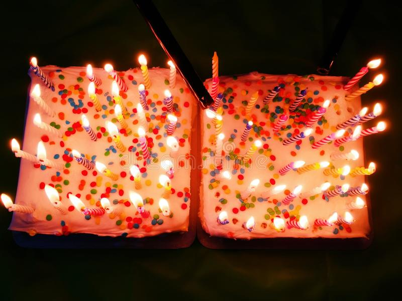 Birthday cakes with candles. Two birthday cakes on the table with candles light up royalty free stock photos
