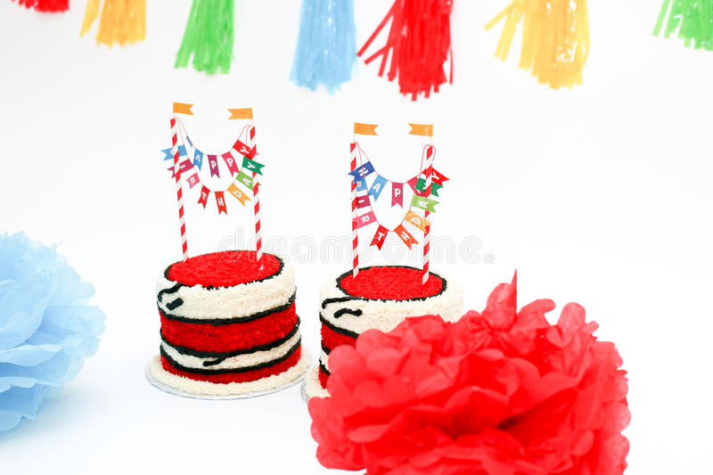 Two birthday cakes for twins. Two birthday cakes with banners and party decorations stock photography