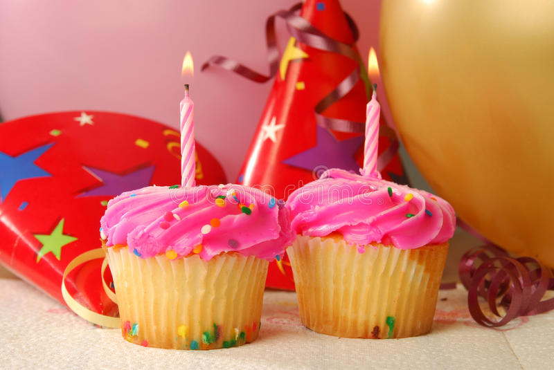 Two Birthday Cupcakes. With candles in a party setting royalty free stock image