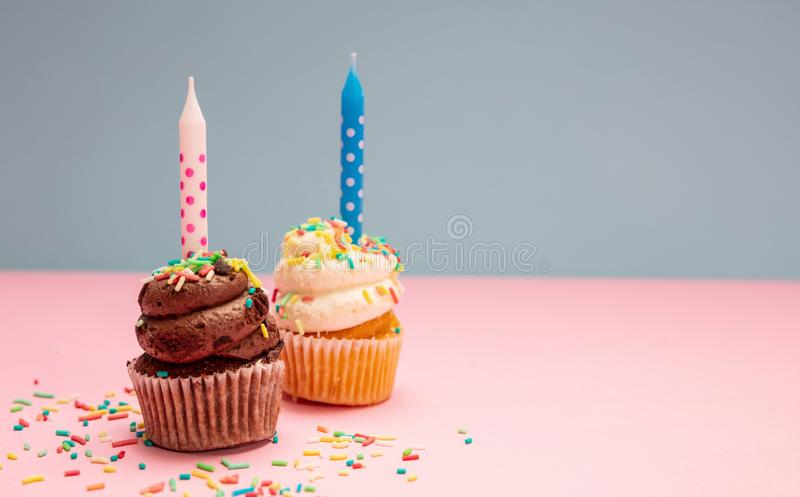 Two birthday cupcakes with candles on blue and pink pastel background, copy space stock photos