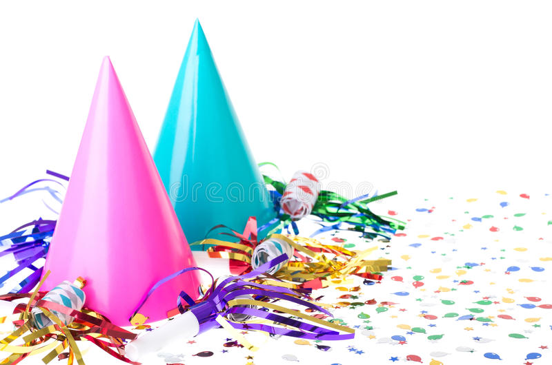 Two Birthday Party Hats. Two colorful birthday party hats with noisemakers and confetti on a white background royalty free stock photo