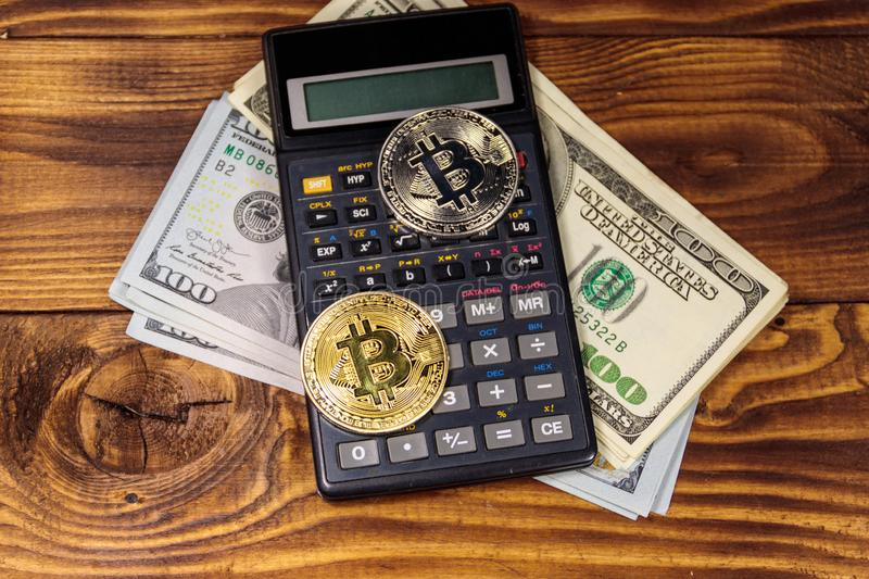 Two bitcoins, calculator and one hundred dollar bills on wooden desk royalty free stock photo