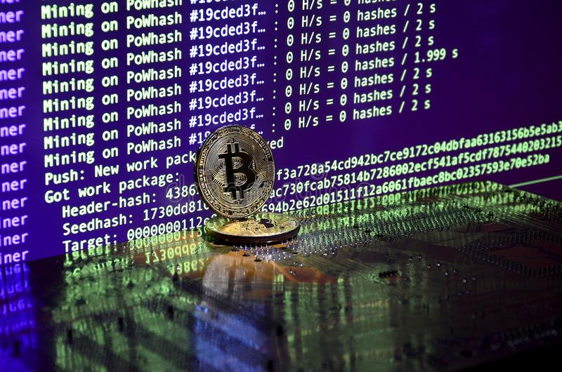 Two bitcoins lies on a videocard surface with background of screen display of cryptocurrency mining by using the GPUs stock photography