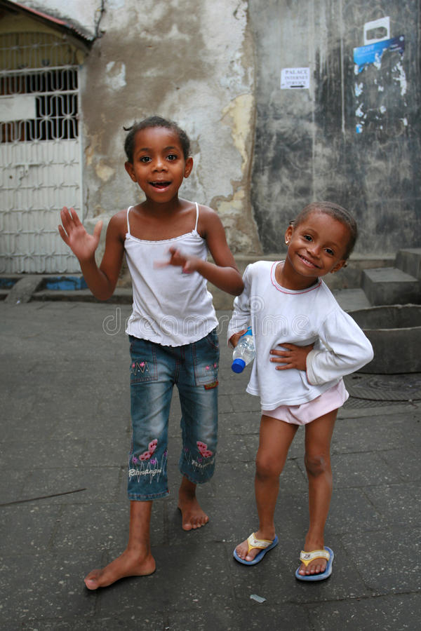 Two black African girls play on the street Stone Town. royalty free stock image