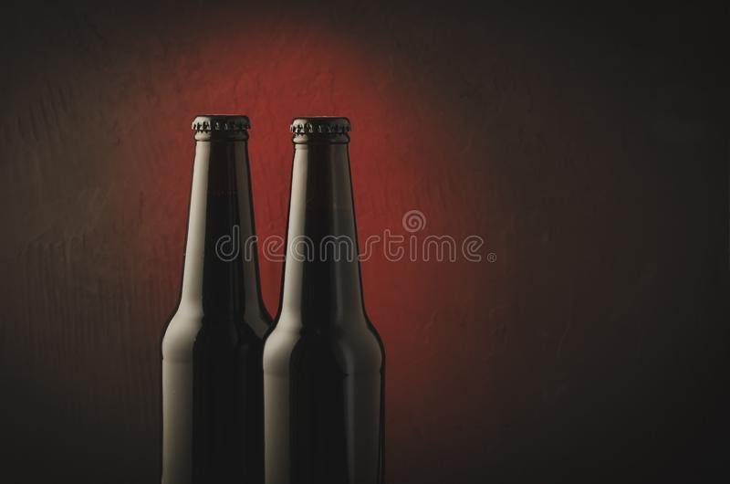Two black bottle of beer on a red background/two black bottle of beer on a red background. Copyspace royalty free stock image
