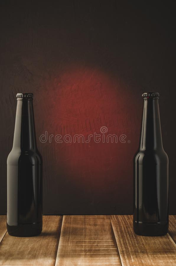 two black bottle of beer on a red background/two black bottle of beer on a red background.  Selective focus and copyspace stock photos