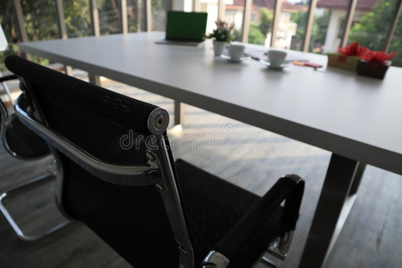 Two black chairs and white table and other stuffs stock image
