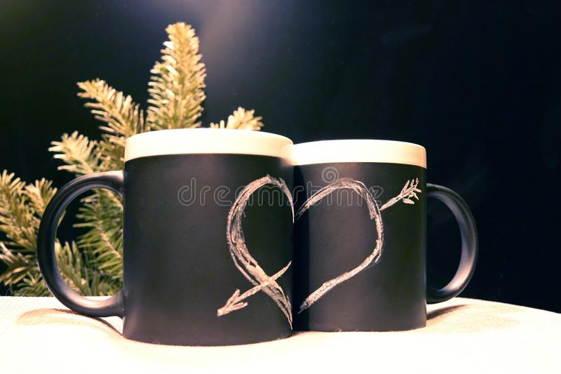 Two black circles with a symbol of love in the dark on the background of the branches of spruce. Heart pierced by an arrow drawn. In white chalk on a black royalty free stock images