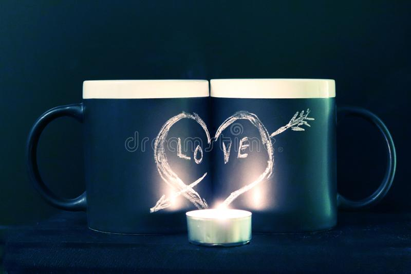 Two black circles with a symbol of love in the dark illuminated by a candle. Heart pierced by an arrow drawn in white chalk on a. Black background. Valentine`s stock photo