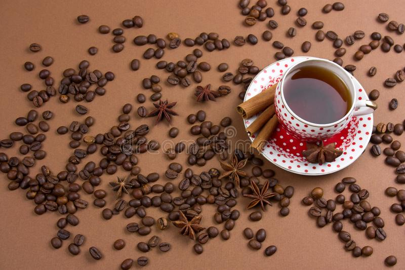 Two black coffee polka dot mugs and coffee beans mess on brown background royalty free stock photos