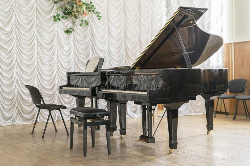 Two black grand pianos on stage. Two black grand pianos on stage royalty free stock photo