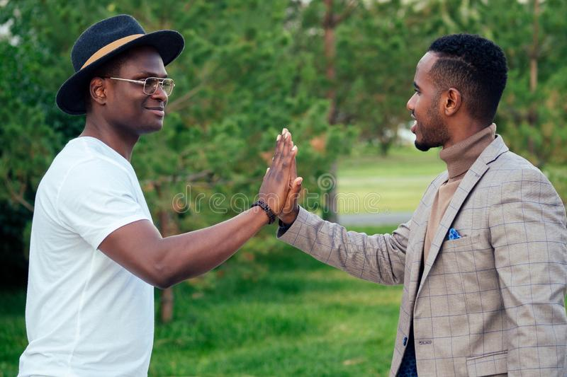 Two black men in stylish suits meeting in a summer park. African-Americans friends hispanic businessman embrace high. Five greeting each other teamwork outdoors stock images