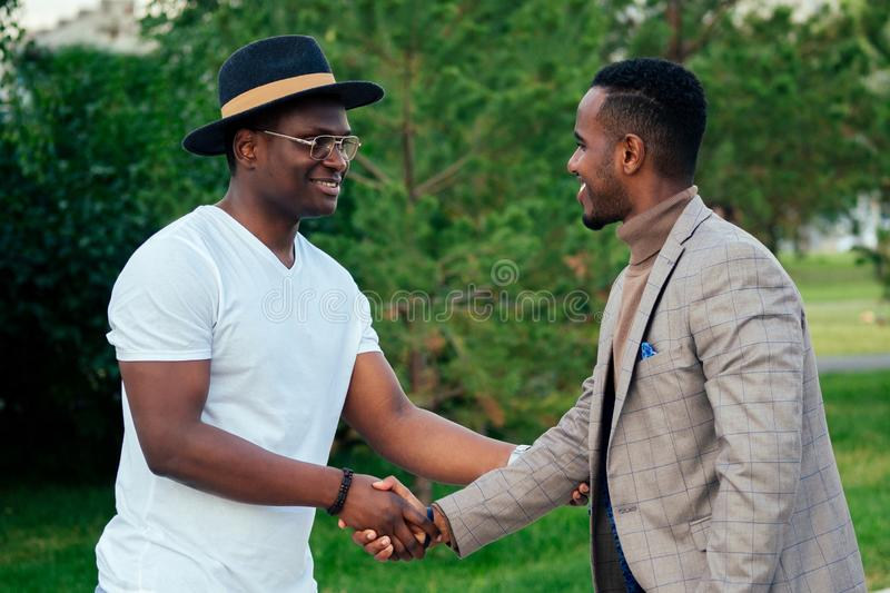 Two black men in stylish suits meeting in a summer park. African-Americans friends hispanic businessman embrace hug. Greeting each other teamwork outdoors stock photography