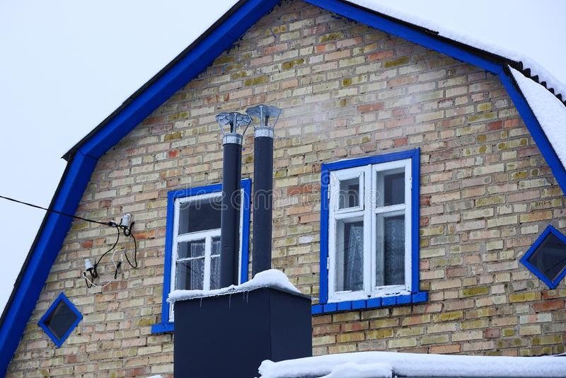 Two black metal chimney pipes on the roof under the snow at the front of a brick wall with windows stock image