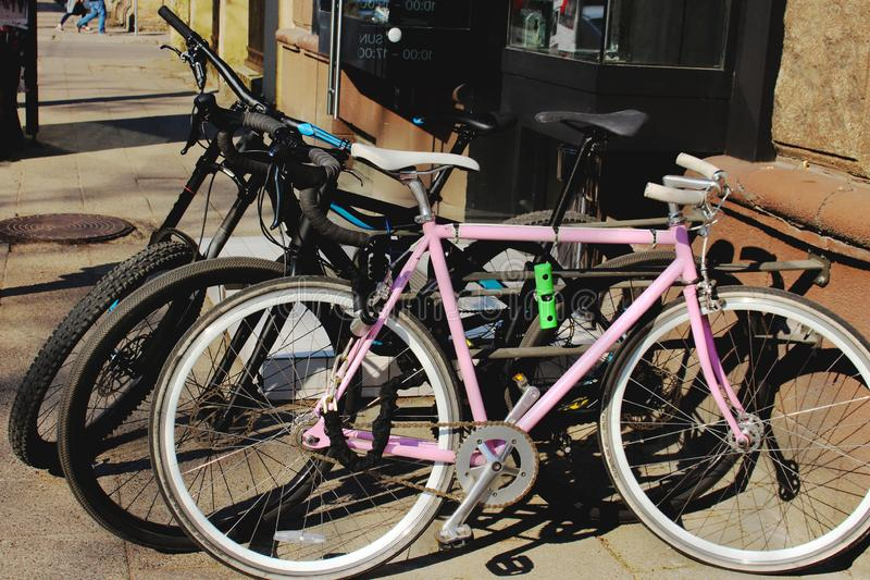 Two black and a pink bicycle parked on city street. On sunny day royalty free stock image