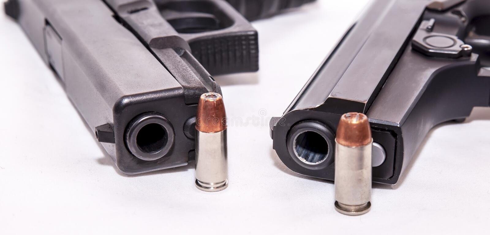 Two black pistols, a 9mm and a 40 caliber each with a bullet to it on front of the muzzle royalty free stock image