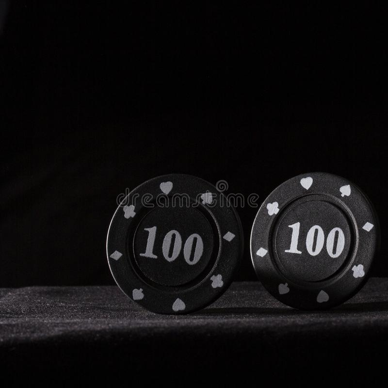 Two black poker chips on a dark background royalty free stock photo
