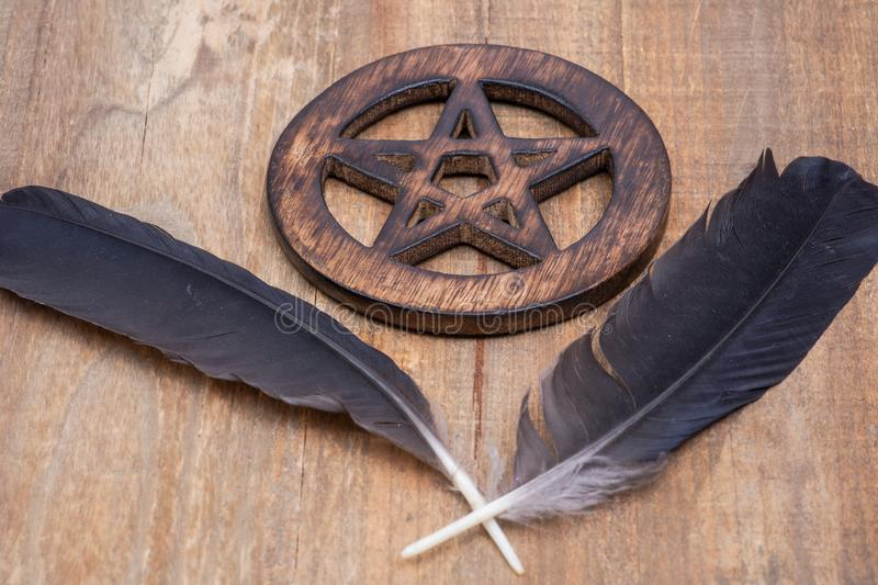 Two Black Raven feathers and Wooden encircled Pentagram symbol on wood. Five elements: Earth, Water, Air, Fire, Spirit. royalty free stock images