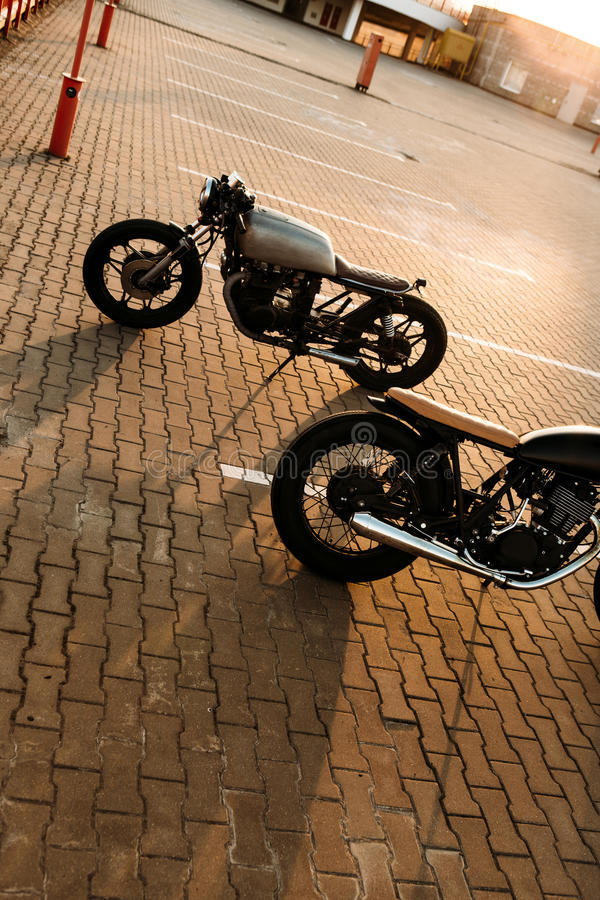 Two black and silver vintage custom motorcycles cafe racers. Two brutal vintage custom motorbike caferacer looking in opposite directions on empty rooftop stock images