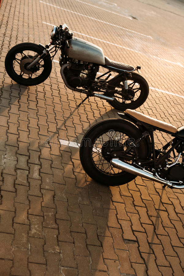 Two black and silver vintage custom motorcycles cafe racers. Two brutal vintage custom motorcycle caferacer looking in opposite directions on empty rooftop royalty free stock images