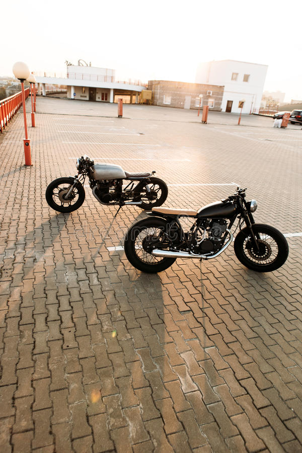 Two black and silver vintage custom motorcycles cafe racers. Two cool vintage custom motorbike caferacer looking in opposite directions on empty rooftop parking stock photos
