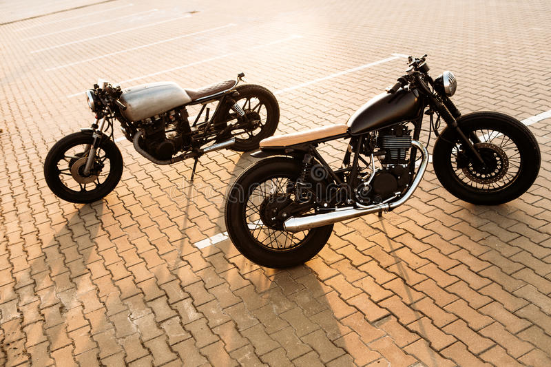 Two black and silver vintage custom motorcycles cafe racers. Two cool vintage custom motorcycle caferacer looking in opposite directions on empty rooftop parking stock photos