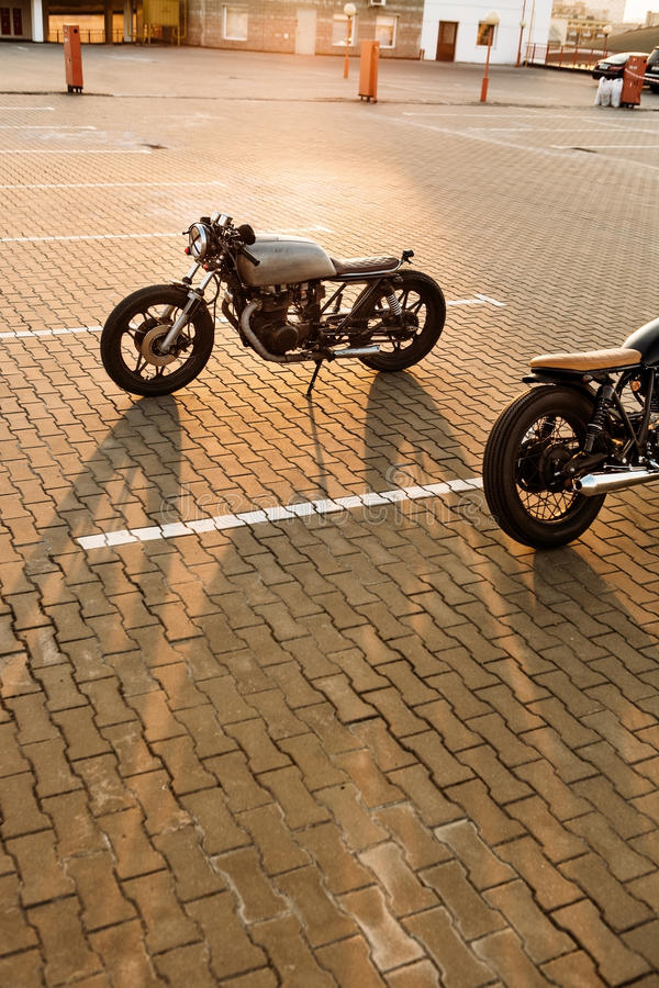 Two black and silver vintage custom motorcycles cafe racers. Two custom vintage motorbike caferacer black and silver motorcycles directed in opposite directions stock images