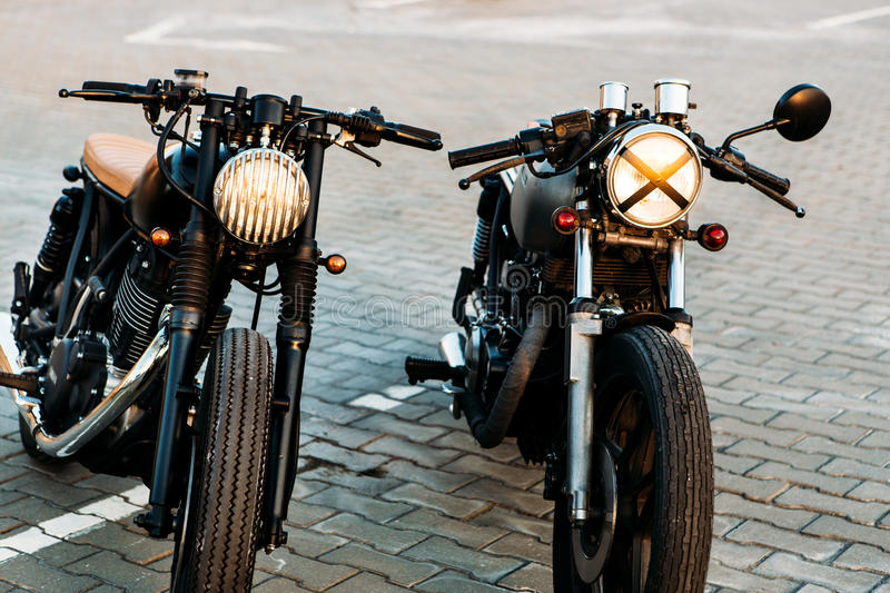 Two black and silver vintage custom motorcycles cafe racers. Vintage custom motorbike caferacer motorcycle with lamp lights turned on. One with grill headlight stock images