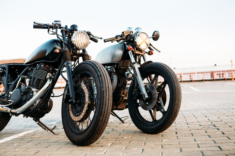 Two black and silver vintage custom motorcycles cafe racers. Two vintage custom motorbike caferacer one with grill headlight another with tape cross over optic royalty free stock photography