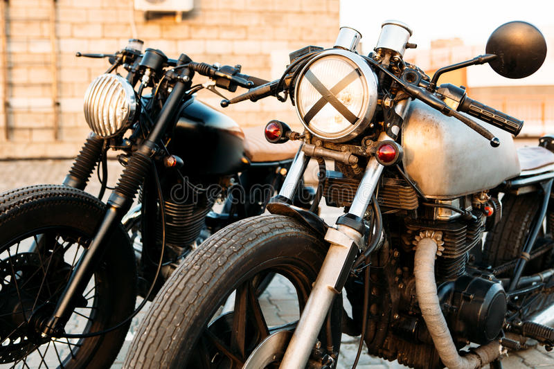 Two black and silver vintage custom motorcycles cafe racers. Two vintage custom motorbike cafe racer motorcycle one with grill headlight another with tape cross royalty free stock photos