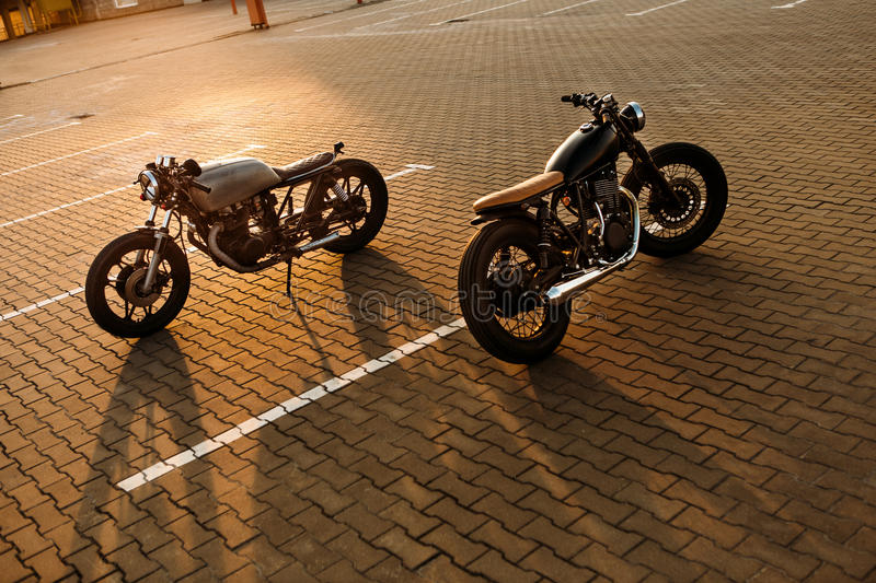 Two black and silver vintage custom motorcycles cafe racers. Two custom vintage motorbikes caferacer black and silver motorcycle directed in opposite directions royalty free stock image