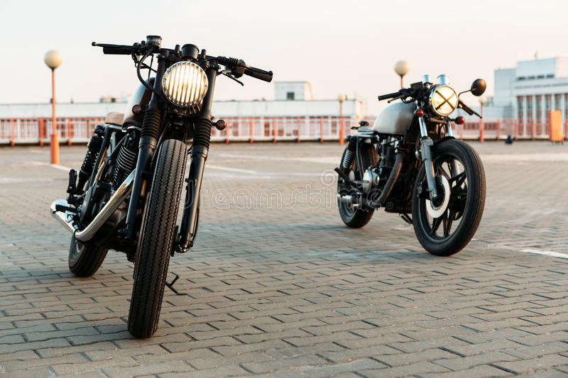 Two black and silver vintage custom motorcycles cafe racers. Vintage custom motorcycle caferacer motorbike with lamp lights turned on. One with grill headlight royalty free stock photography