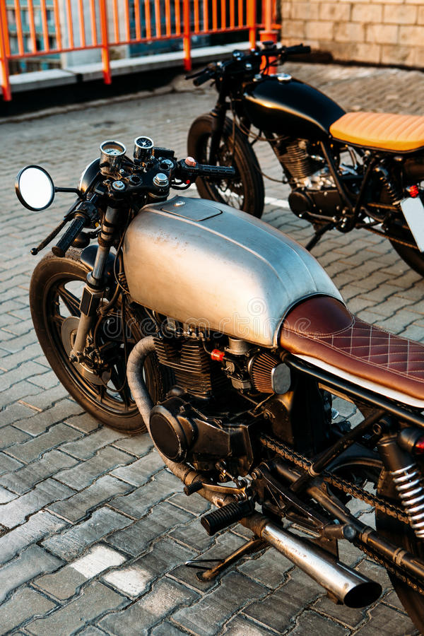 Two black and silver vintage custom motorcycles cafe racers. Two vintage custom motorcycle caferacer motorbike looking in same direction on empty rooftop parking royalty free stock images