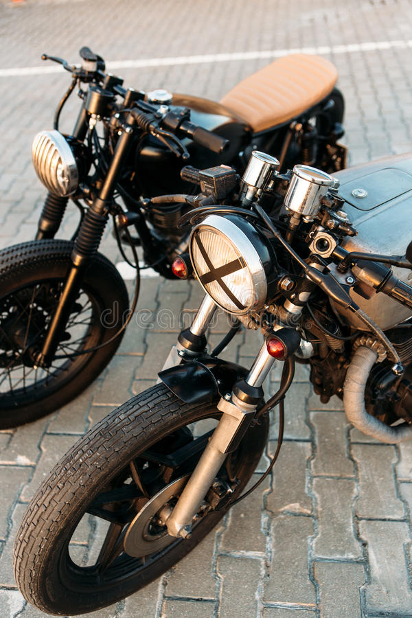 Two black and silver vintage custom motorcycles cafe racers. Two vintage custom motorcycle caferacer motorbike one with grill headlight another with tape cross stock photos