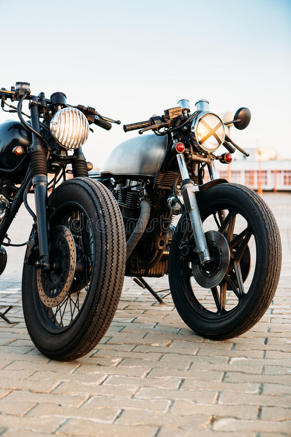 Two black and silver vintage custom motorcycles cafe racers. Two vintage custom motorcycle caferacer one with grill headlight another with tape cross over optic royalty free stock image