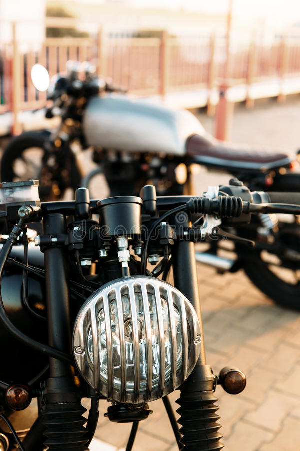 Two black and silver vintage custom motorcycles cafe racers. Two vintage custom motorbike caferacer looking in opposite directions on empty rooftop parking lot royalty free stock photos