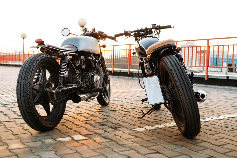 Two black and silver vintage custom motorcycles caferacers. Back view of two vintage custom motorbike cafe racer motorcycle looking in same direction on empty royalty free stock images