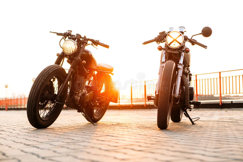 Two black and silver vintage custom motorcycles caferacers. Front view of two vintage custom motorbike caferacer motorcycle one with grill headlight another with stock photography