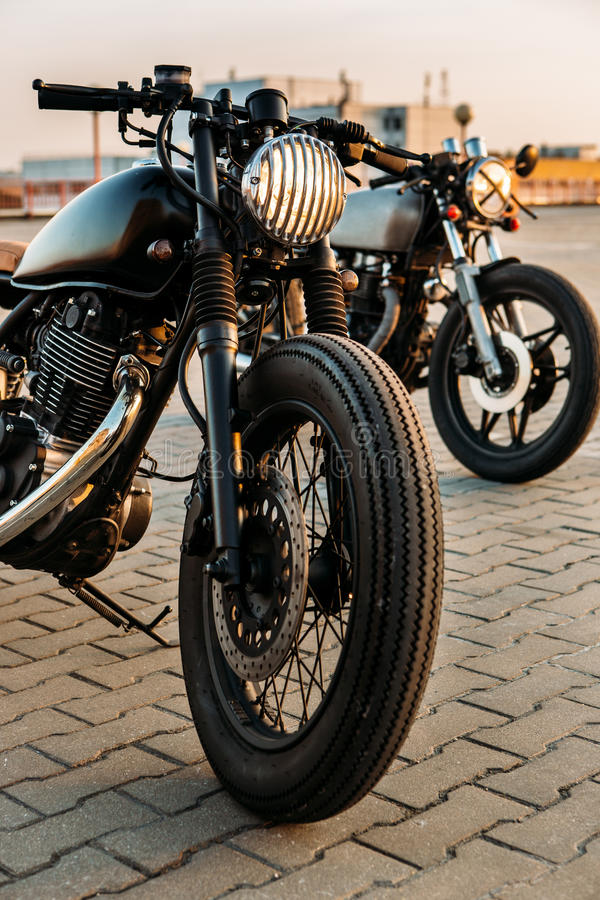 Two black and silver vintage custom motorcycles caferacers. Vintage custom motorbike cafe racer motorcycle with lamp lights turned on. One with grill headlight royalty free stock photos