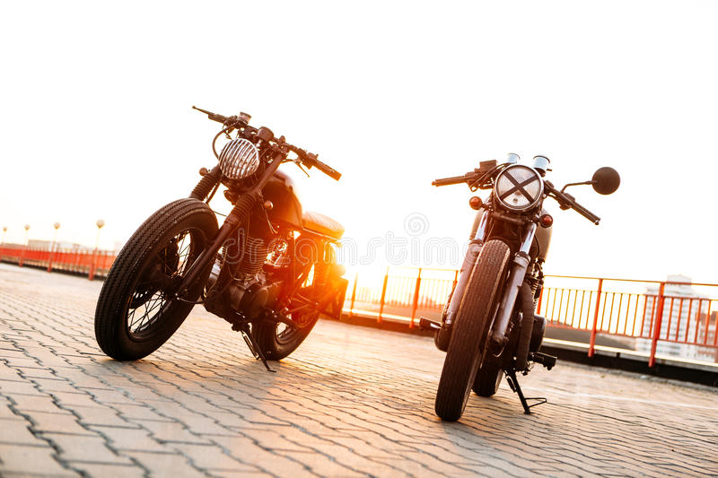 Two black and silver vintage custom motorcycles caferacers. Two vintage custom motorbike cafe racer one with grill headlight another with tape cross over optic stock photo