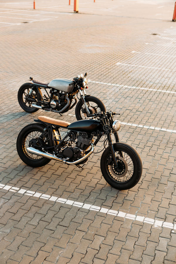Two black and silver vintage custom motorcycles caferacers. Custom vintage motorbike caferacer motorcycle with lamp lights turned on. One with grill headlight royalty free stock photo