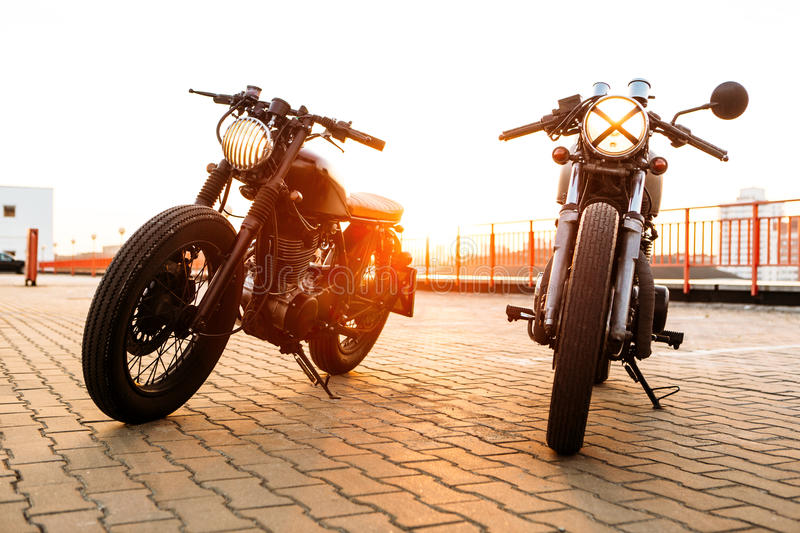 Two black and silver vintage custom motorcycles caferacers. Two vintage custom motorbike caferacer one with grill headlight another with tape cross over optic on royalty free stock photos