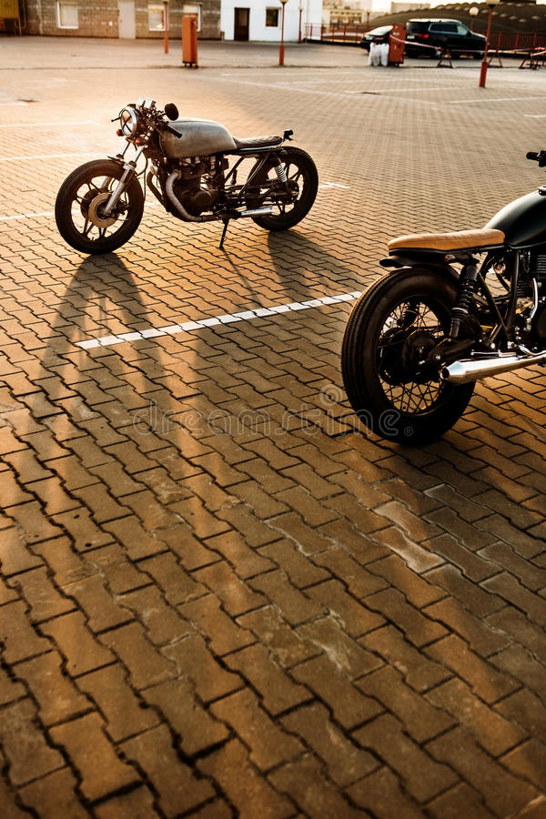 Two black and silver vintage custom motorcycles caferacers. Two custom vintage motorbikes caferacer silver and black motorcycle directed in opposite directions stock photos