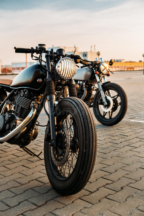 Two black and silver vintage custom motorcycles caferacers. Vintage custom motorcycle caferacer motorbike with lamp lights turned on. One with grill headlight stock image