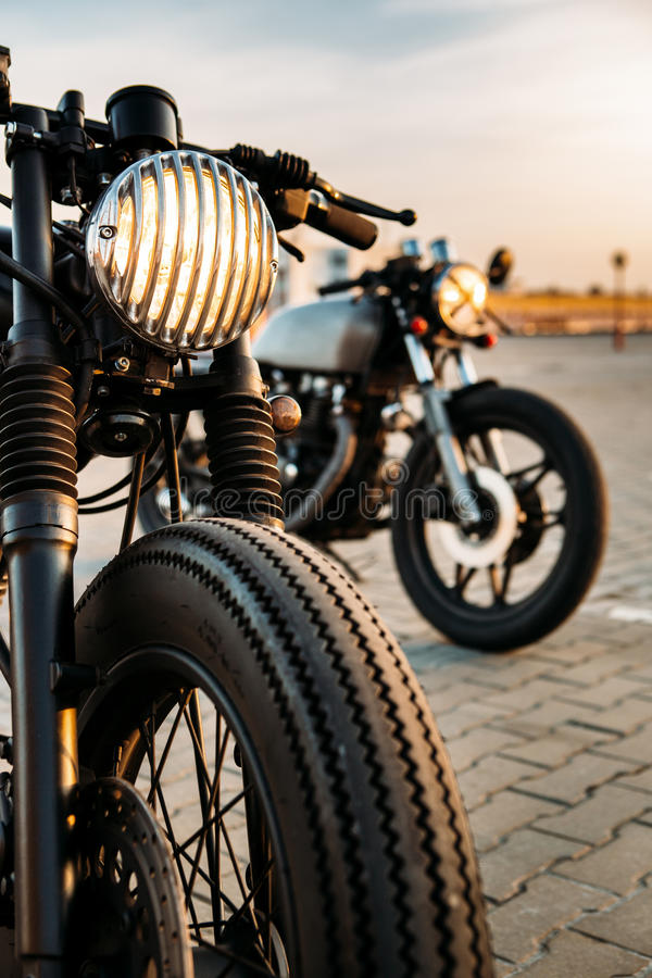 Two black and silver vintage custom motorcycles caferacers. Vintage custom motorcycle caferacer motorbike with lamp lights turned on. One with grill headlight stock photography