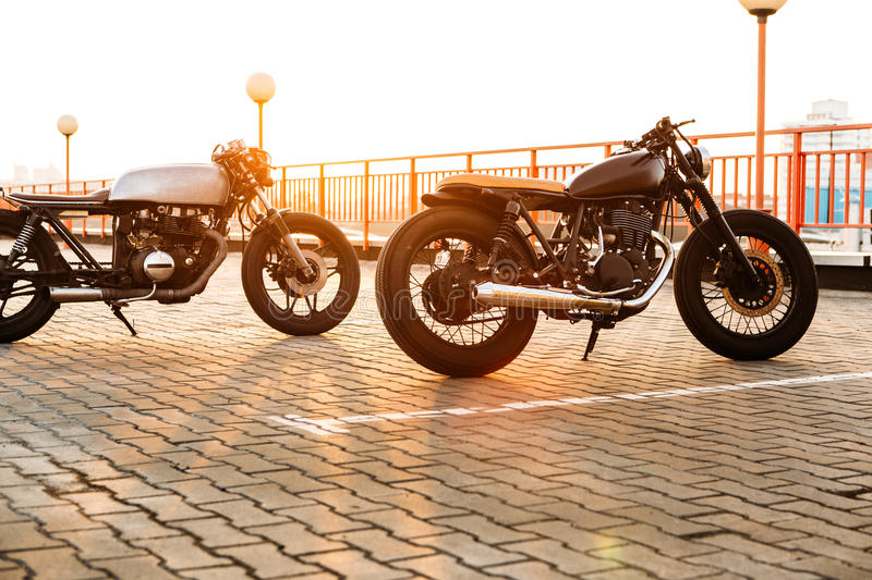 Two black and silver vintage custom motorcycles caferacers. Two vintage custom motorcycle caferacer motorbike looking in same direction on empty rooftop parking royalty free stock image