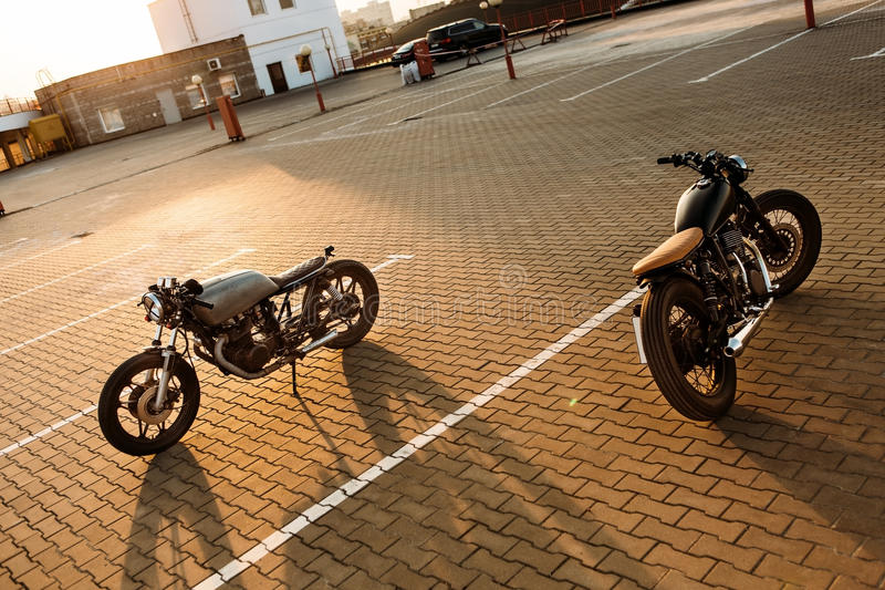 Two black and silver vintage custom motorcycles caferacers. Two vintage custom motorcycle caferacer silver and black motorbikes directed in opposite directions royalty free stock image