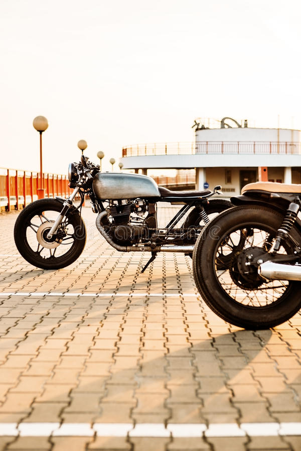 Two black and silver vintage custom motorcycles caferacers. Two vintage custom motorcycle caferacer motorbikes on empty rooftop parking lot surrounded by urban stock photo
