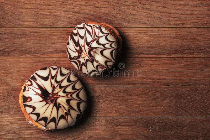 Two black and white buns on a dark wooden background stock image